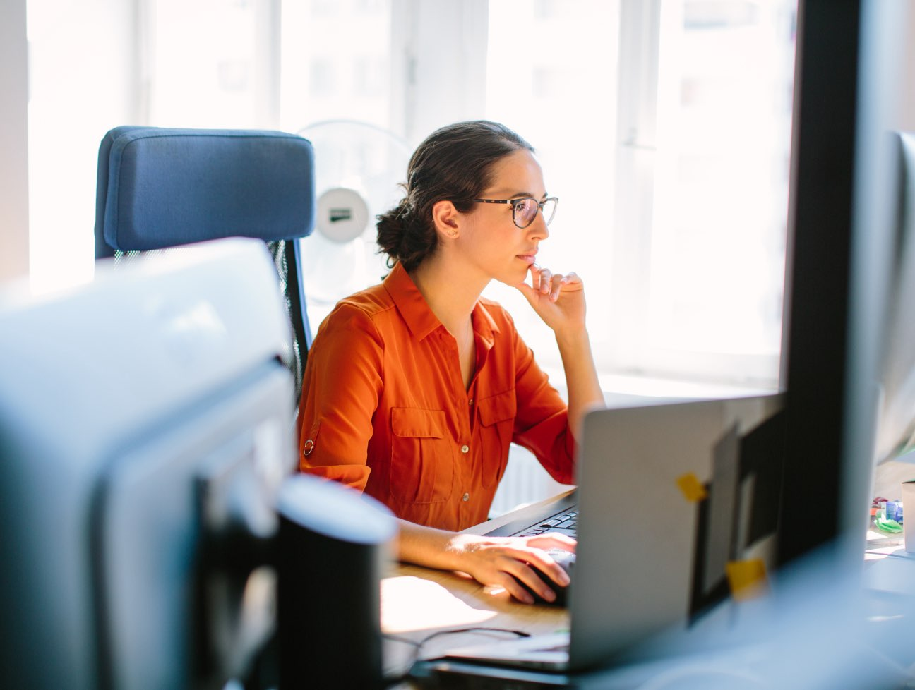 Woman wearing orange shirt and glasses staring off into her computer