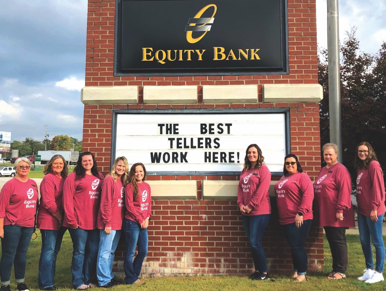 A group of Equity Bank employees flanking an exterior bank sign.