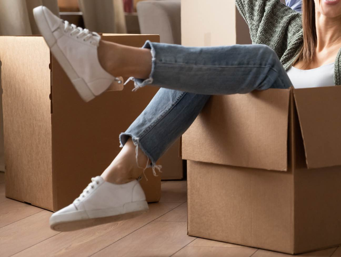 Woman sitting in cardboard moving box, kicking feet out