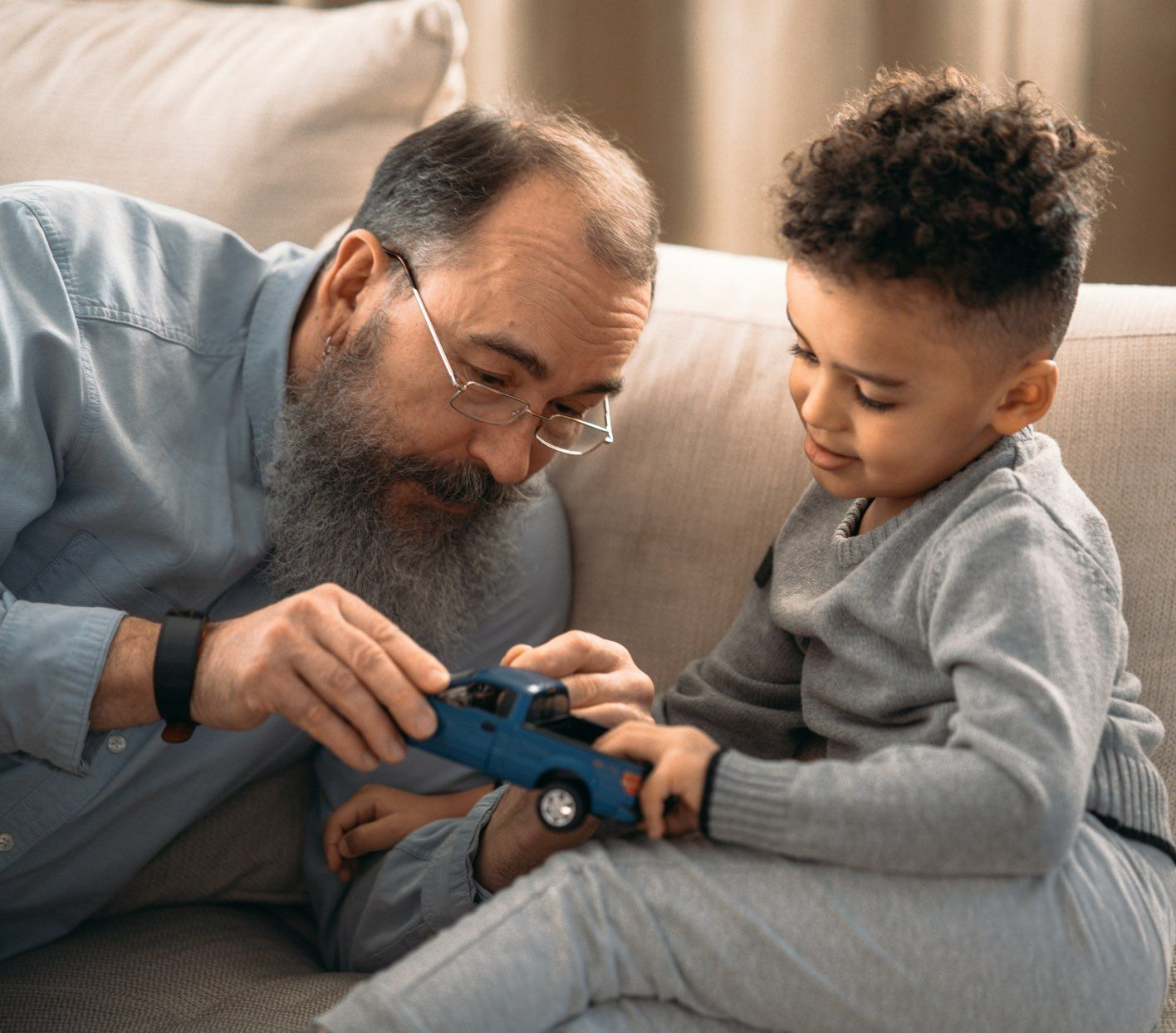 Grandfather playing with young grandson on couch.