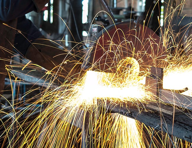 Sparks flying from worker cutting metal.